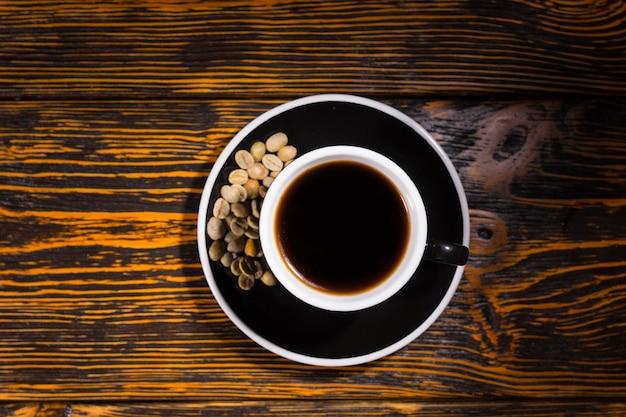 Ansicht von oben nach unten von kaffee mit bohnen in untertasse
