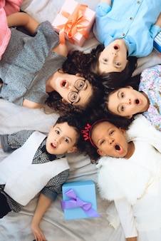 Ansicht von oben. porträt von fröhlichen kindern, die auf dem boden liegen.
