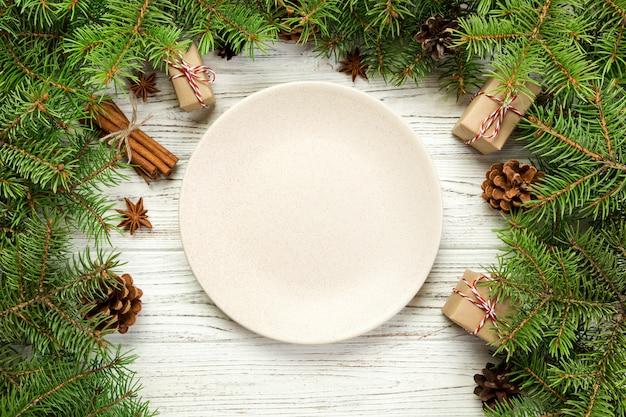 Ansicht von oben. rundes keramisches der leeren platte auf hölzernem weihnachtshintergrund. feiertagsabendessenteller mit dekor des neuen jahres