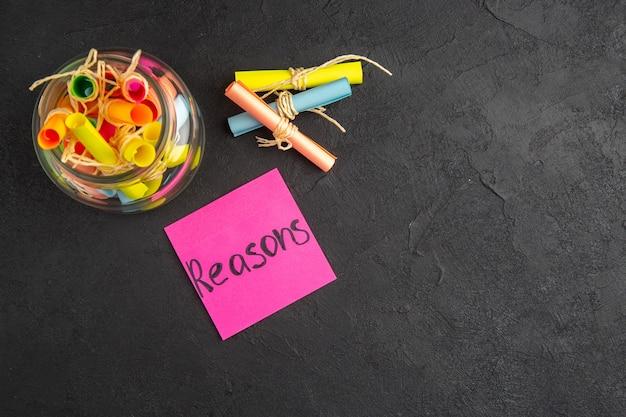 Ansicht von oben scrollen farbige wunschpapiere in glasgründen auf haftnotiz auf dunklem hintergrund mit freiem speicherplatz geschrieben