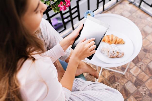Ansicht von oben tablette in den händen des mädchens im pyjama, das auf balkon sitzt und am morgen frühstückt.