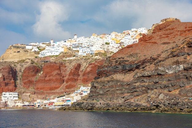 Ansicht von oia-dorf mit weißen häusern auf rotem felsenkessel von santorini-insel, griechenland