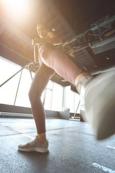 Ansicht von unten auf eine sportliche frau in sportkleidung, die beim training mit dem bein tritt