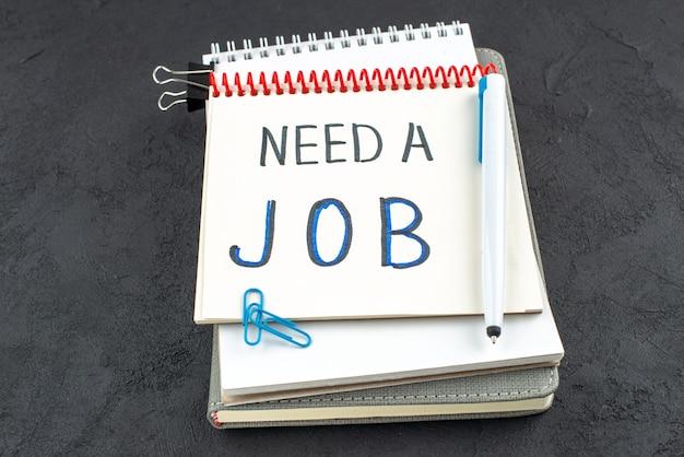 Ansicht von unten benötigen einen job, der auf einem spiralnotizbuch mit blauem stift, edelsteinclips, binderclips auf dunklem hintergrund, geschrieben wird