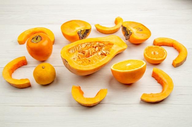 Ansicht von unten butternut-kürbis halbieren kaki mandarine auf weißem holztisch