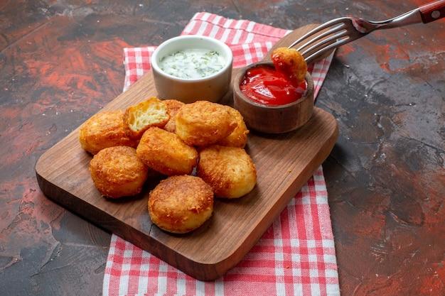 Ansicht von unten chicken nuggets auf holzbrett mit saucen nugget auf gabel auf dunklem tisch