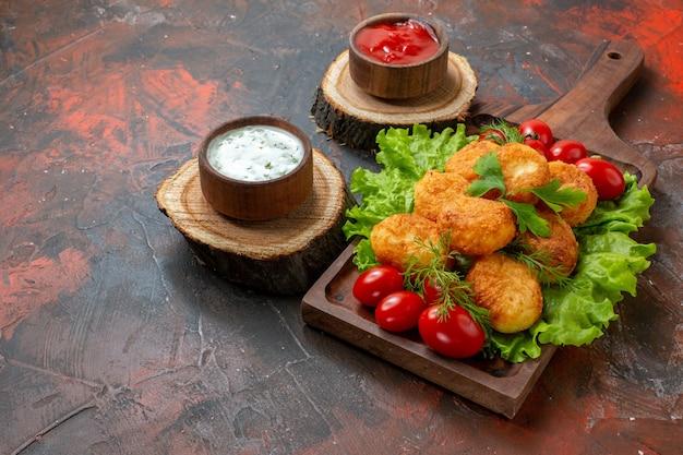 Ansicht von unten chicken nuggets salat kirschtomaten auf holzbrett saucen in schalen auf holzbrettern auf dunklem tisch
