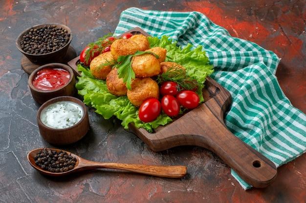 Ansicht von unten chicken nuggets salat kirschtomaten auf holzbrett schwarzer pfeffer in schüssel saucen in kleinen holzschalen holzlöffel auf dunklem tisch