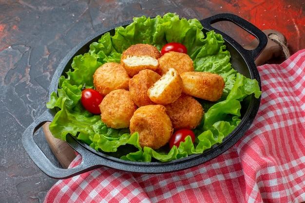 Ansicht von unten chicken nuggets salat kirschtomaten in pfanne auf dunkelrotem hintergrund