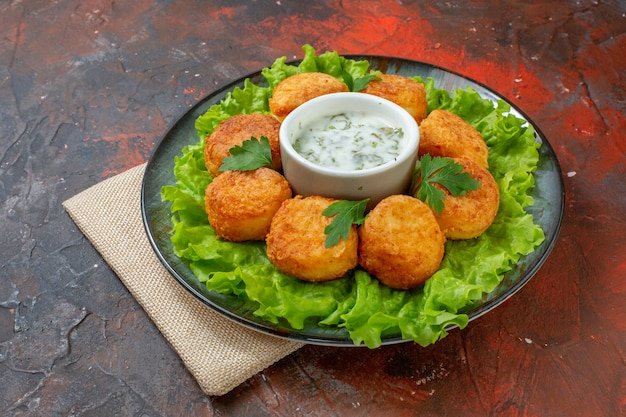 Ansicht von unten chicken nuggets salat und sauce auf teller auf dunkelrotem tisch
