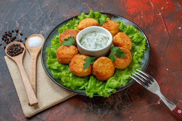 Ansicht von unten chicken nuggets salatgabel auf teller salz und schwarzer pfeffer in holzlöffeln auf dunklem tisch