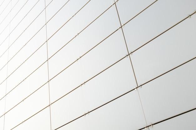 Ansicht von unten der weißmetallwand eines gebäudes gemacht von den kleinen rechtwinkligen metallblättern