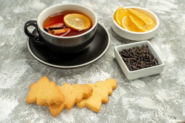 Ansicht von unten eine tasse tee mit zitrone und zimtstangen keksschale mit schokolade auf grauer oberfläche