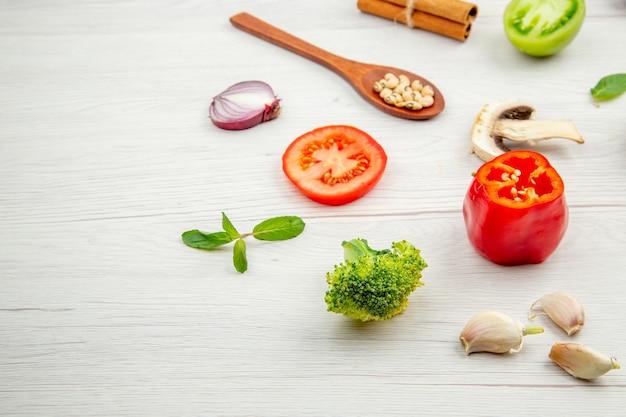 Ansicht von unten frisch geschnittenes gemüse holzlöffel pilze grüne und rote tomaten zwiebel brokkoli knoblauch auf grauem tisch freien platz