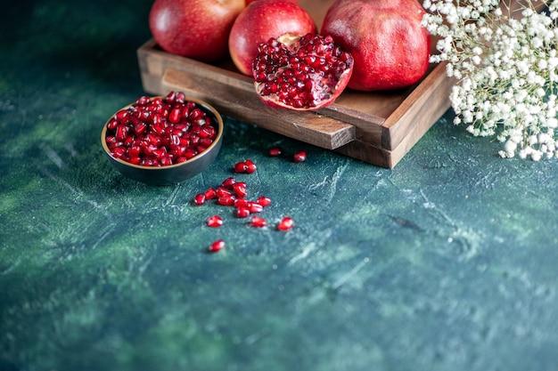Ansicht von unten frische granatäpfel auf holzbrett blumen auf tisch freiraum