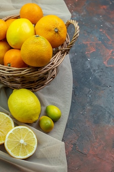 Ansicht von unten frische mandarinen im weidenkorb geschnittene zitronen cumcuat auf tüll auf dunkelrotem grund