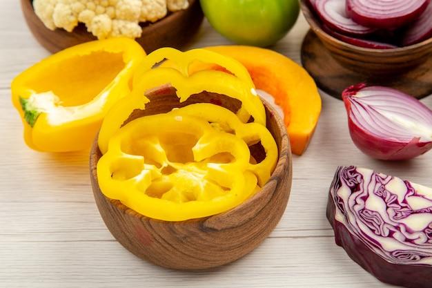 Ansicht von unten frisches gemüse gelbe paprika rotkohl blumenkohl kürbisse geschnittene zwiebeln in schalen auf weißem holztisch