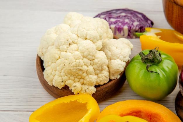 Ansicht von unten frisches gemüse grüne tomaten geschnitten rotkohl gelbe paprika blumenkohl in schüssel auf weißem holztisch