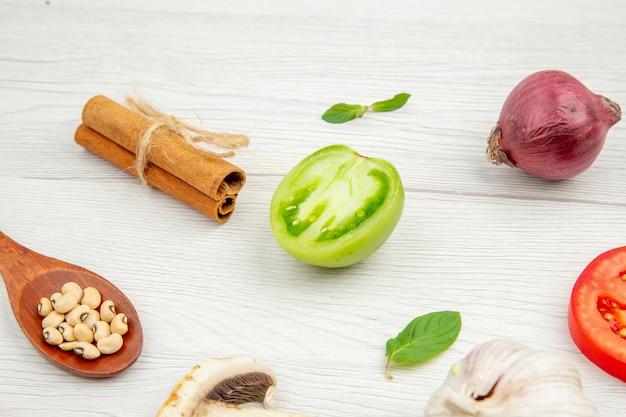 Ansicht von unten frisches gemüse holzlöffel pilz grüne und rote tomaten zwiebel zimtstangen knoblauch auf grauem tisch