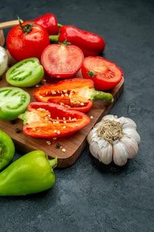Ansicht von unten frisches gemüse pilze rote und grüne tomaten paprika auf schneidebrett knoblauch schwarzer pfeffer in schüssel auf dunklem tisch