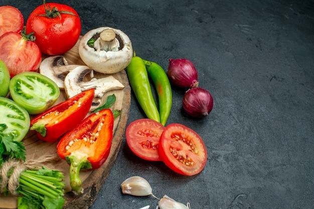 Ansicht von unten frisches gemüse pilze rote und grüne tomaten paprika grüns auf rustikalem brett peperoni knoblauchzwiebeln auf dunklem tisch frei platz