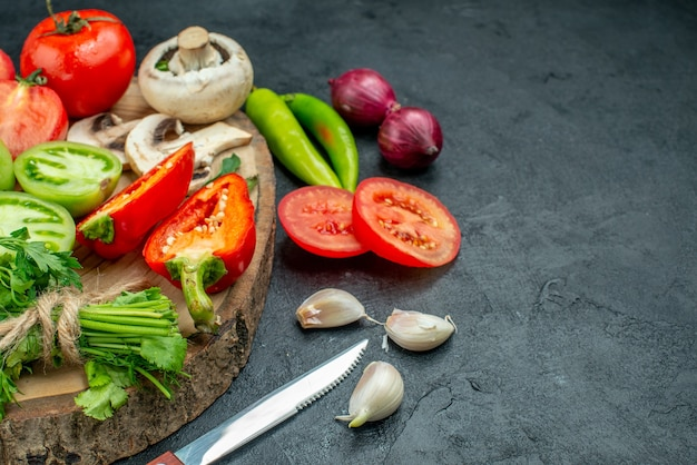 Ansicht von unten frisches gemüse pilze rote und grüne tomaten paprika grüns auf rustikalem brett peperoni messer knoblauch auf dunklem tisch freiraum