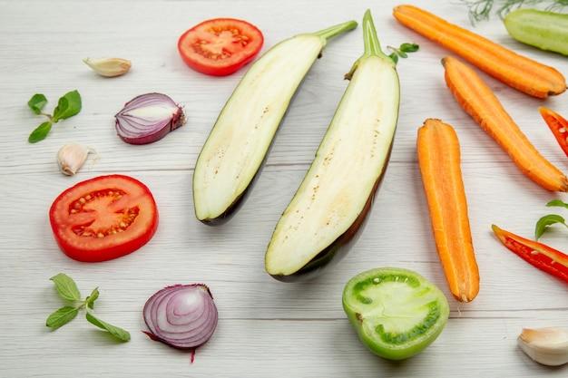 Ansicht von unten gehacktes gemüse gurke aubergine tomate karotte zwiebel pfeffer auf grauem holztisch