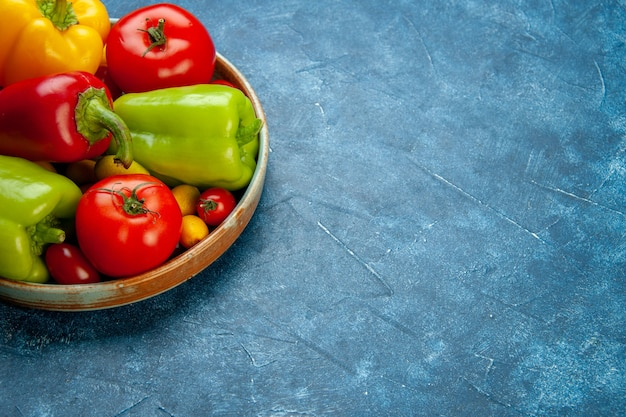 Ansicht von unten gemüse kirschtomaten verschiedene farben paprika tomaten auf holzplatte auf blauer oberfläche freier platz