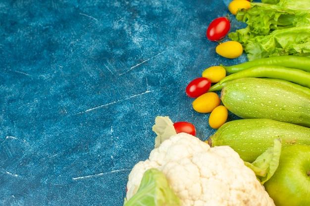 Ansicht von unten gemüse kirschtomaten zacchini cumcuat grüne peperoni salat blumenkohl auf blauem tisch mit freiem platz