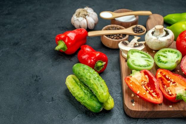 Ansicht von unten gemüse pilze rote und grüne tomaten rote paprika auf schneidebrett knoblauch schwarzer pfeffer und salz in schalen holzlöffel gurken auf dunklem tisch kopie raum