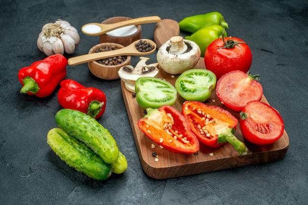 Ansicht von unten gemüse pilze rote und grüne tomaten rote paprika auf schneidebrett knoblauch schwarzer pfeffer und salz in schalen holzlöffel gurken auf dunklem tisch