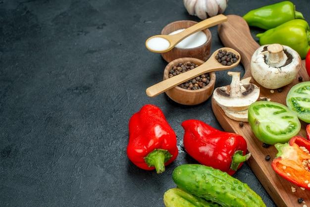 Ansicht von unten gemüse pilze tomaten rote paprika auf schneidebrett knoblauch schwarzer pfeffer und salz in schalen holzlöffel gurken auf dunklem tisch mit kopie platz