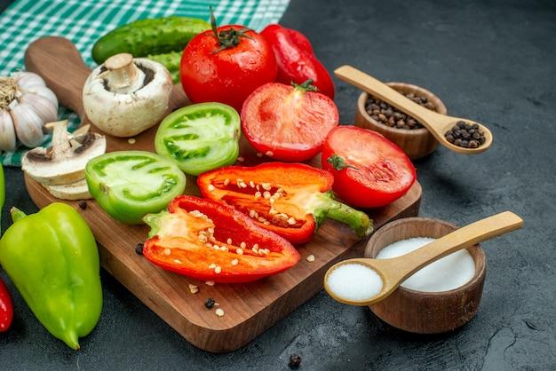 Ansicht von unten gemüse pilze tomaten rote paprika auf schneidebrett knoblauch schwarzer pfeffer und salz in schalen holzlöffel gurken auf schwarzem tisch