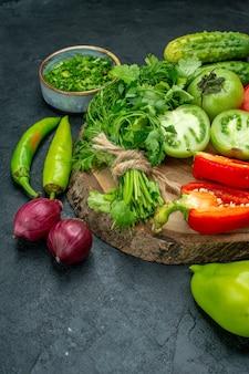 Ansicht von unten gemüse tomaten paprika gurken grüns auf holzbrett peperoni rote zwiebeln auf schwarzem tisch