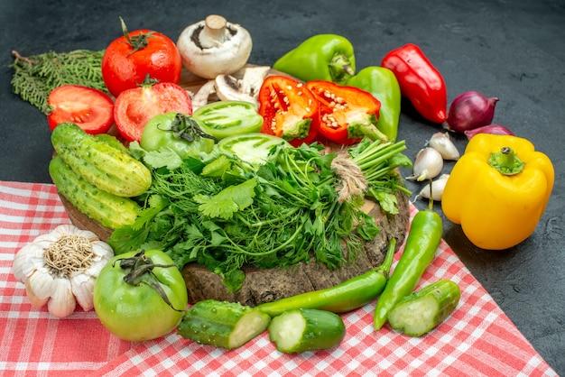 Ansicht von unten gemüse tomaten rote paprika grüns auf holzbrett peperoni knoblauch auf tischdecke auf schwarzem tisch