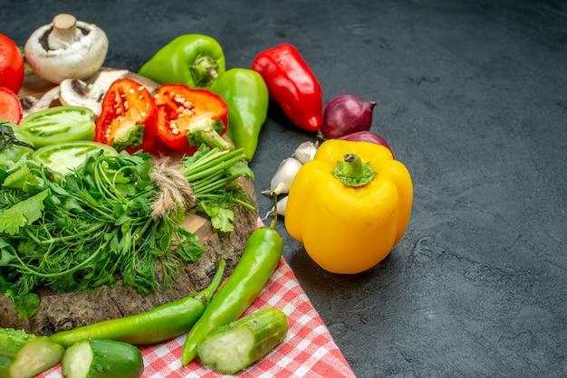 Ansicht von unten gemüse tomaten rote paprika grüns auf rustikalem brett peperoni auf tischdecke auf schwarzem tisch