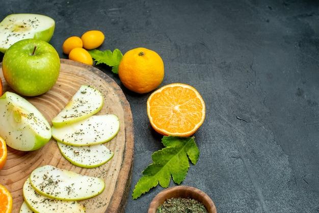 Ansicht von unten geschnittene äpfel und mandarinen auf rundem holzbrett cumcuat getrocknetes minzpulver in holzschale auf dunklem tisch mit freiem platz