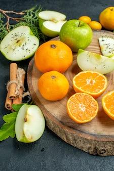 Ansicht von unten geschnittene äpfel und mandarinen auf rustikalem servierbrett zimtstangen cumcuat auf dunklem tisch