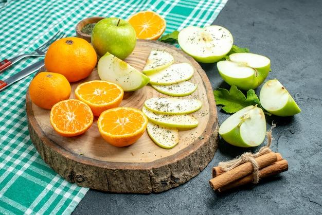 Ansicht von unten geschnittene äpfel und mandarinen mit getrocknetem minzpulver auf holzbrett-zimtstangen auf grüner tischdecke auf dunklem tisch