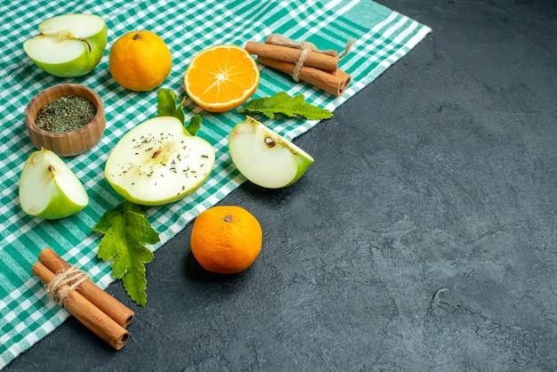 Ansicht von unten geschnittene äpfel und mandarinen zimtstangen getrocknetes minzpulver in schüssel auf grüner tischdecke auf dunklem tischkopierraum