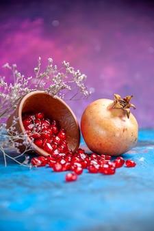 Ansicht von unten granatapfelkerne in einer schüssel ein granatapfel auf lila freiem platz