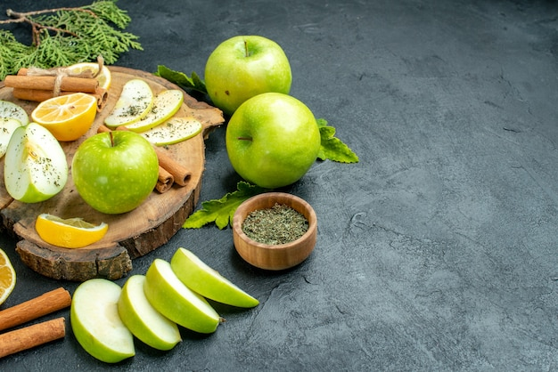 Ansicht von unten grüne äpfel zimtstangen und zitronenscheiben apfelscheiben auf holzbrett geschnittene zitronen getrocknete minzschüssel auf schwarzem tischfreiraum