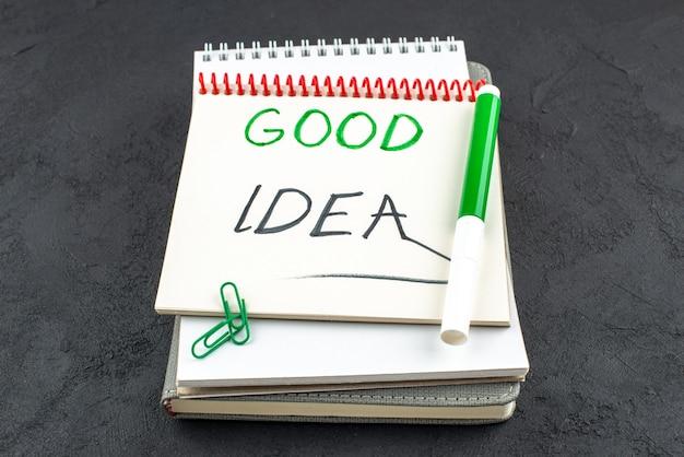 Ansicht von unten gute idee geschrieben auf spiralnotizbuch grüne markierungen edelsteinclips auf dunklem hintergrund