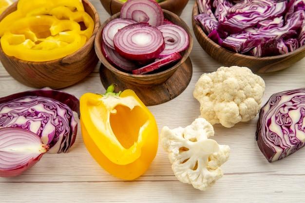 Ansicht von unten holzschalen mit geschnittenem gemüse blumenkohl paprika zwiebel rotkohl auf weißem holztisch