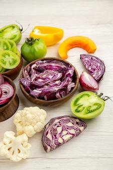 Ansicht von unten holzschalen mit geschnittenem gemüse blumenkohl rotkohl grüne tomaten kürbis auf weißem holztisch