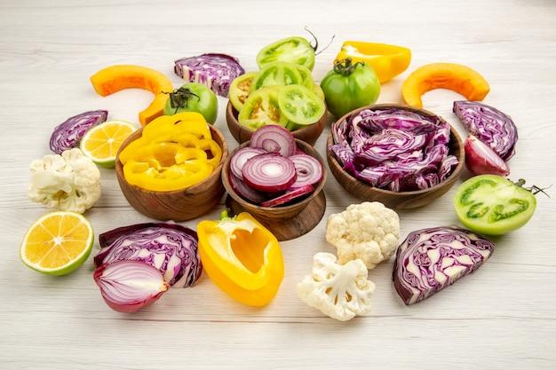 Ansicht von unten holzschalen mit geschnittenem gemüse blumenkohl zwiebel rotkohl grüne tomaten kürbis auf weißer oberfläche stockfoto