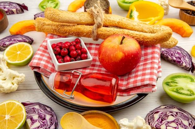 Ansicht von unten hundsrose beeren in schüssel apfelbrot rote flasche auf serviette auf rundem teller geschnittenes gemüse auf weißem tisch