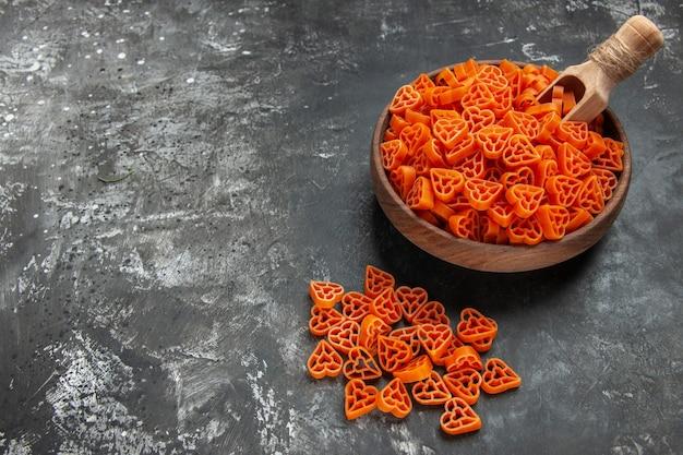Ansicht von unten italienische pasta rote herzen in einem schüssel holzlöffel auf dunkler oberfläche