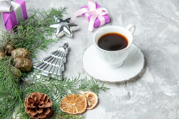 Ansicht von unten kiefernzweige tasse tee getrocknete zitronenscheiben tannenzapfen kleine geschenke auf grauem hintergrund