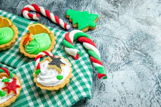 Ansicht von unten kleine weihnachtstörtchen auf tischdecke weihnachtssüßigkeiten auf grauem tischfreiraum